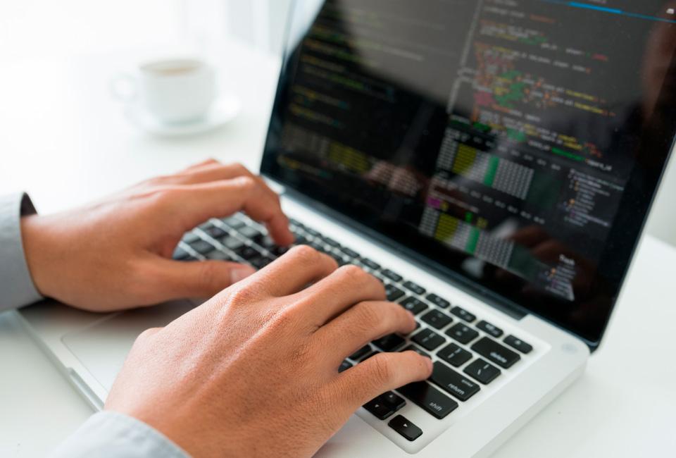 Imagem em close das mãos de um programador trabalhando em seu notebook.