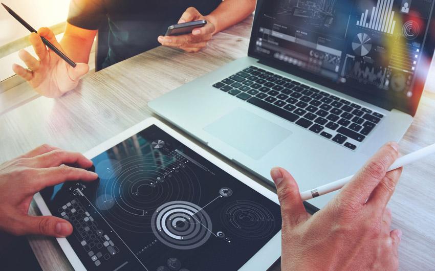 Imagem em close das mãos de dois homens interagindo e utilizando tablet, notebook e smartphone durante um projeto.