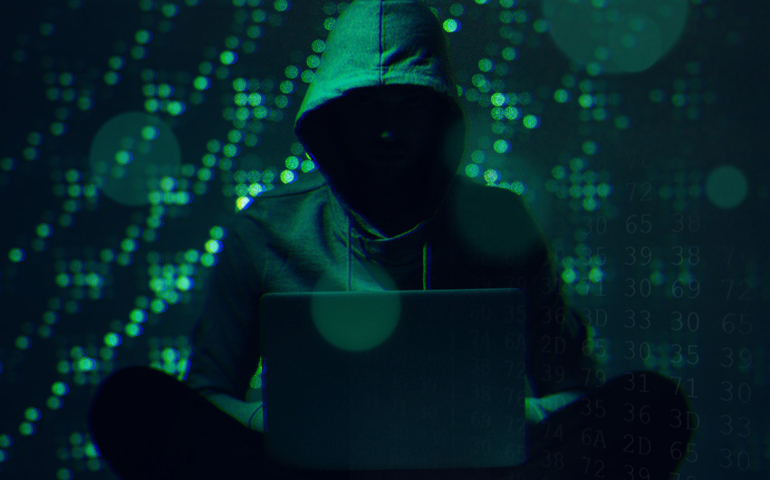 Imagem sombria de um hacker com o rosto oculto nas sombras